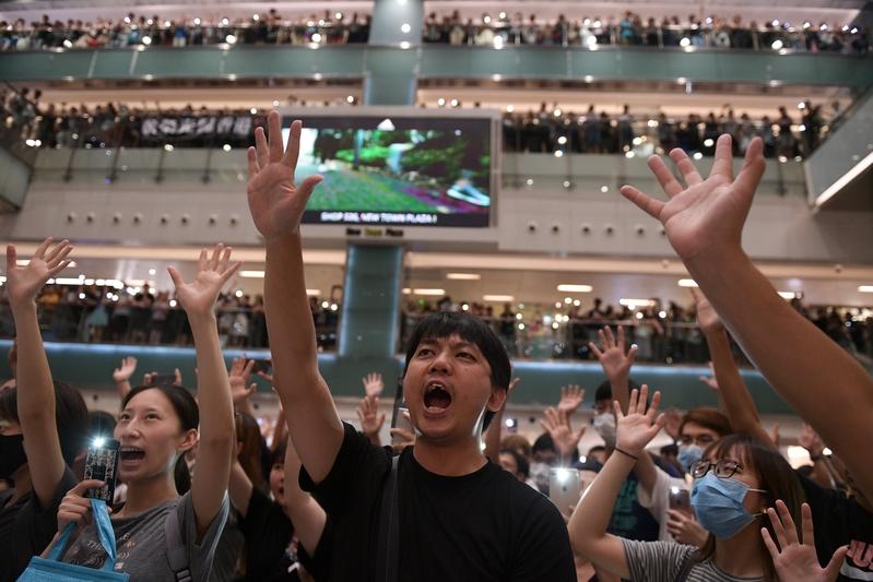 2019年9月11日,香港市民在沙田新城市廣場齊唱「願榮光歸香港」,市民抬起手臂,展開手掌,代表五大訴求缺一不可。(NICOLAS ASFOURI/AFP/Getty Images)