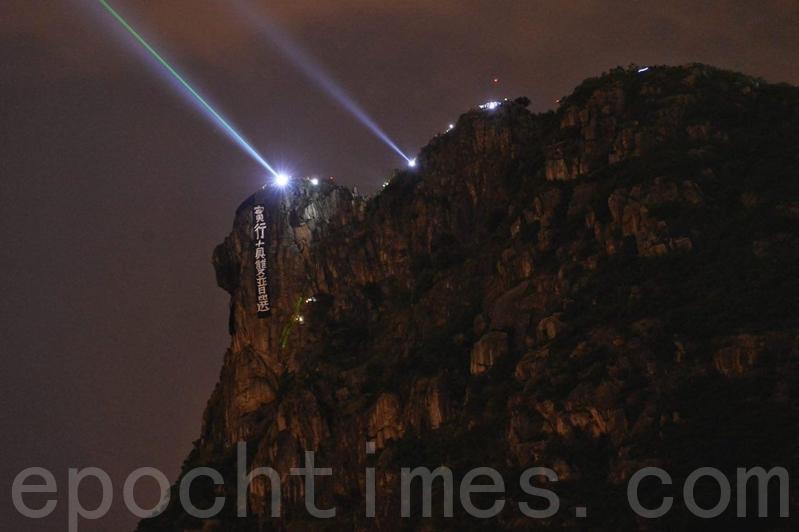 2019年9月13日,香港市民在獅子山與太平山的人群用雷射筆及閃光燈互相照射,並在獅子山掛上「實施真雙普選」訴求。(宋碧龍/大紀元)