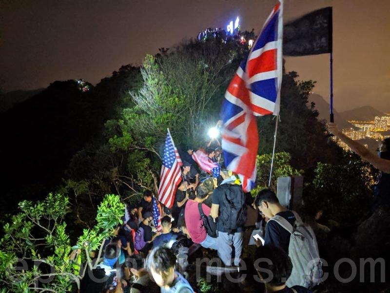 2019年9月13日,香港市民在獅子山拿美、英國旗築起燈光人鏈。(黃曉翔/大紀元)