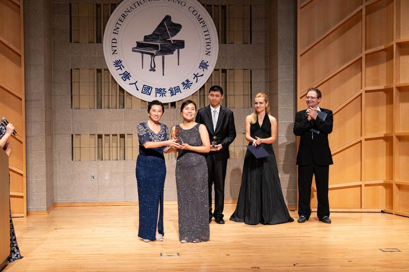 2019年9月28日,第五屆新唐人國際鋼琴大賽獲獎名單揭曉,新唐人系列大賽組委會主席馬麗娟(左一)向銅獎得主李祥僖(shanghie Lee)頒發獎盃。(戴兵/大紀元)