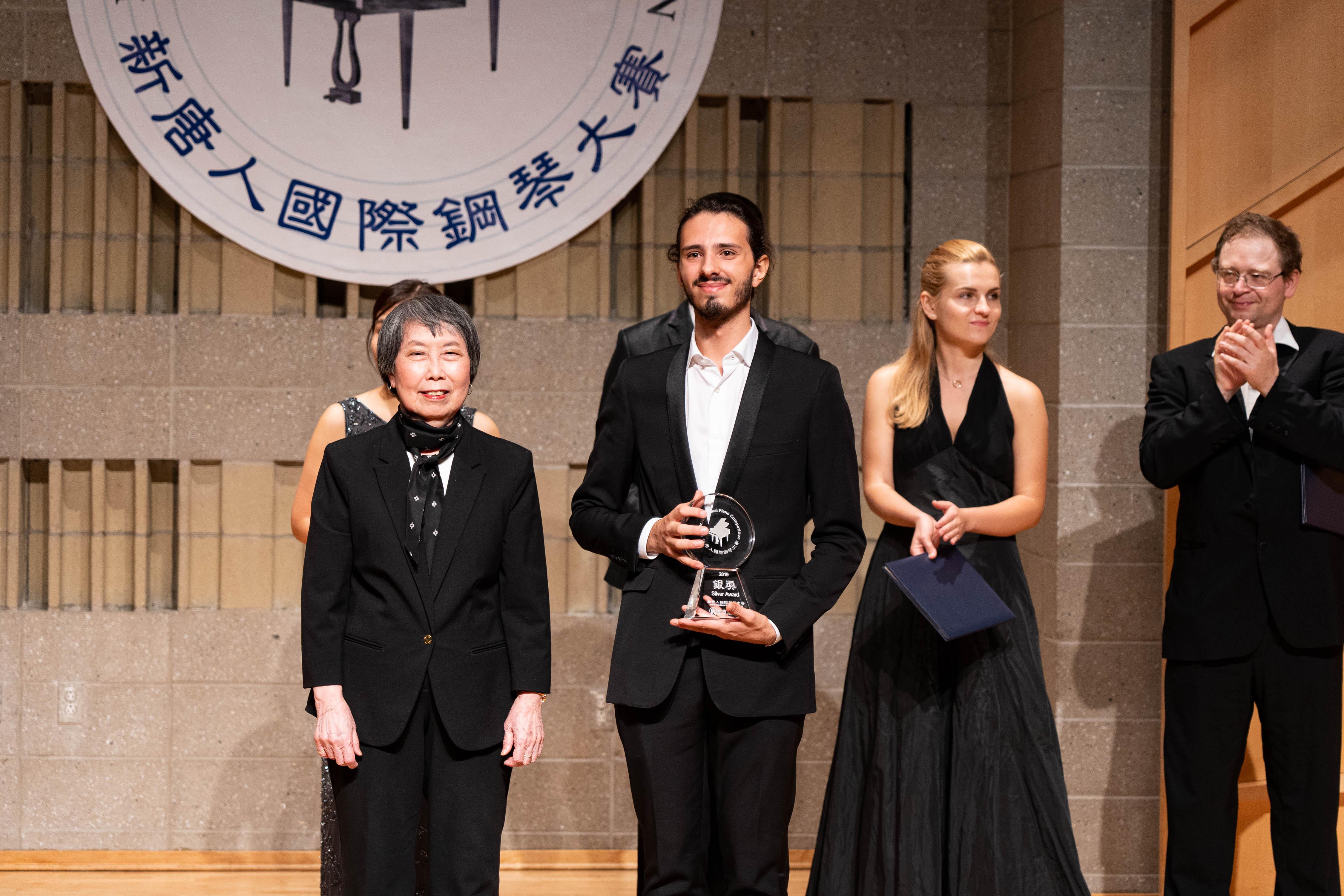 2019年9月28日,第五屆新唐人國際鋼琴大賽獲獎名單揭曉,本次大賽評委會主席姚妼姬教授(左一)向銀獎得主基阿科米利(Nicolas Giacomelli)頒發獎盃。(戴兵/大紀元)