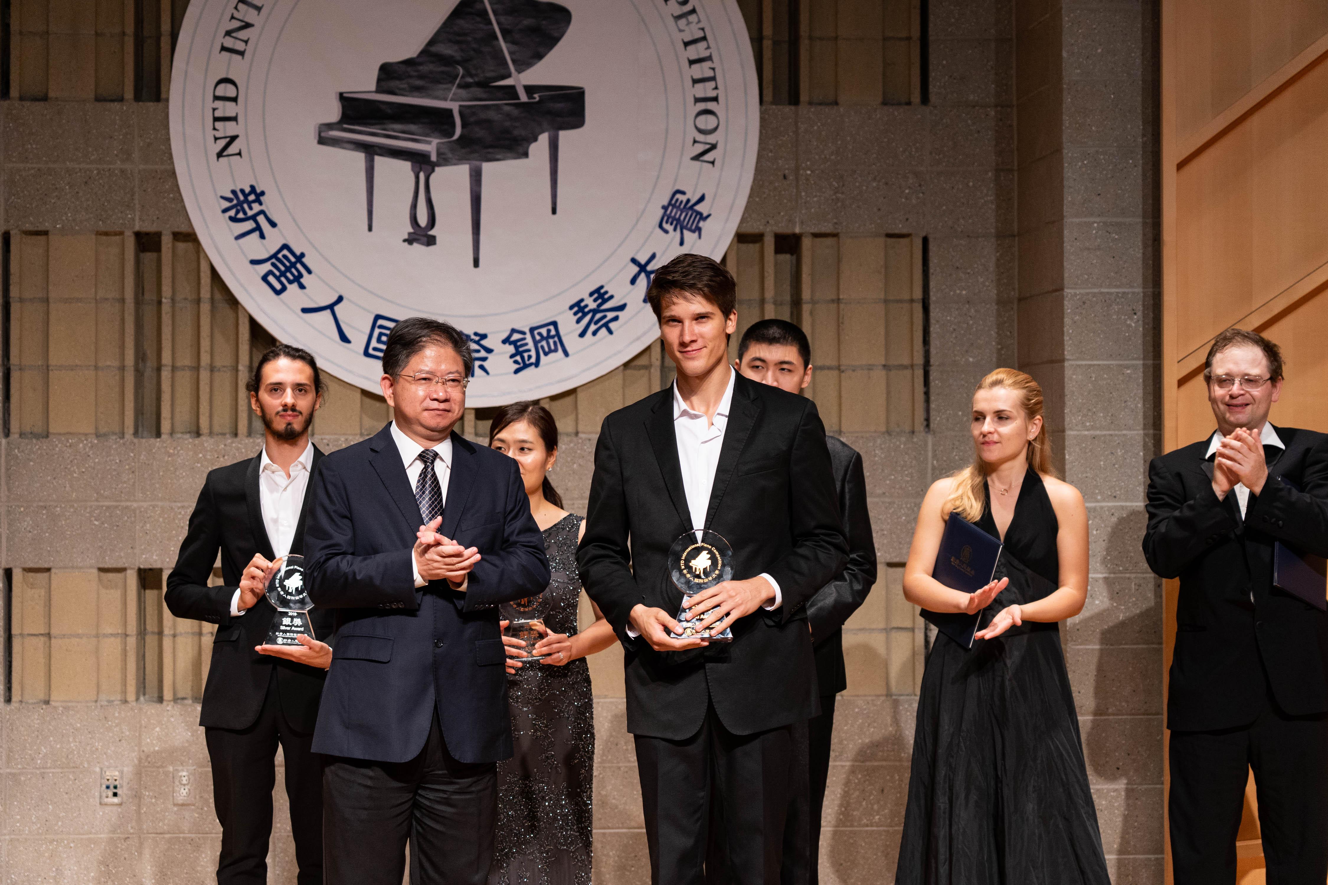 2019年9月28日,第五屆新唐人國際鋼琴大賽獲獎名單揭曉,大紀元時報、新唐人電視台媒體集團總裁唐忠先生(左一)向金獎得主彼得羅夫(Vladimir Petrov)頒發獎盃。(戴兵/大紀元)