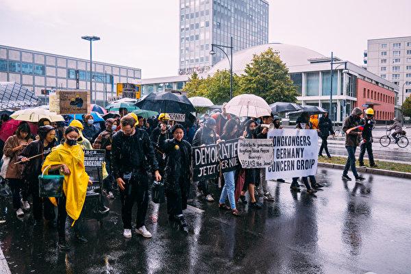 9月28日下午數百旅德港人和德國各界人士在首都柏林舉行集會遊行,抗議中共暴政,支持港人爭取自由民主。圖為遊行隊伍不懼風雨前行,從前東柏林市中心的亞歷山大廣場走到中使館。(張清颻/大紀元)
