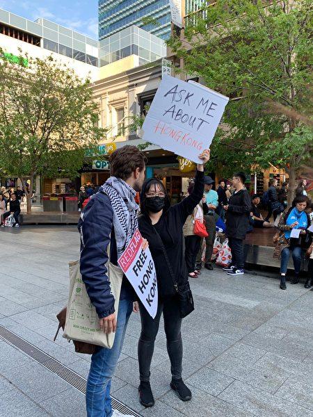 2019年9月29日,澳洲阿德雷德香港青年背後背著「請你問我關於香港的事」的牌子。(陽洋/大紀元)