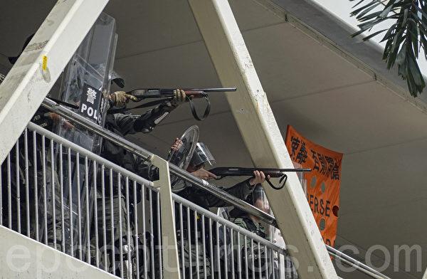 2019年9月29日,全球24個國家、65個城市舉行「全球連線-共抗極權」遊行,圖為香港,遊行隊伍經過灣仔遭遇警方暴力清場,有警察於天橋上俯射抗爭者。(余鋼/大紀元)