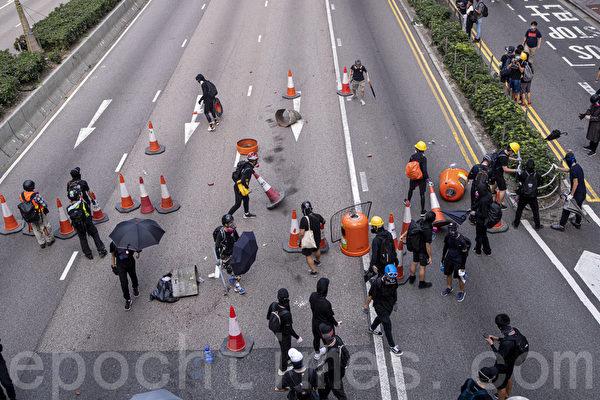 2019年9月29日,全球24個國家、65個城市舉行「全球連線-共抗極權」遊行,圖為香港,遊行隊伍經過灣仔遭遇警方暴力清場,有抗爭者在道路上設置路障。(余鋼/大紀元)