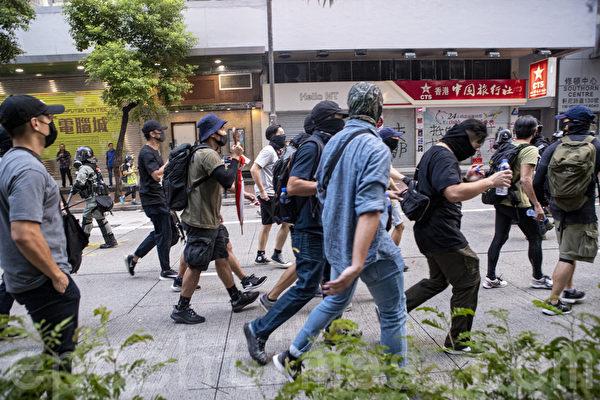 2019年9月29日,全球24個國家、65個城市舉行「全球連線-共抗極權」遊行。圖為香港,遊行隊伍經過灣仔遭遇警方暴力清場,有警察裝扮成抗爭者向灣仔地鐵站離去。(余鋼/大紀元)