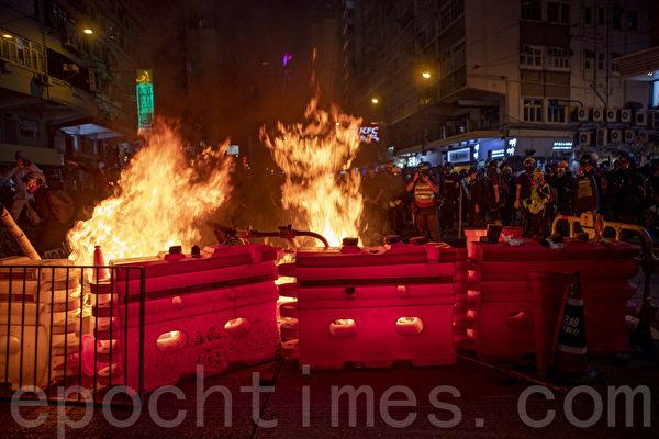 2019年9月29日,全球24個國家、65個城市舉行「全球連線-共抗極權」遊行,圖為香港,遊行隊伍經過灣仔遭遇警方武力清場,民眾燃燒障礙物。(余鋼/大紀元)