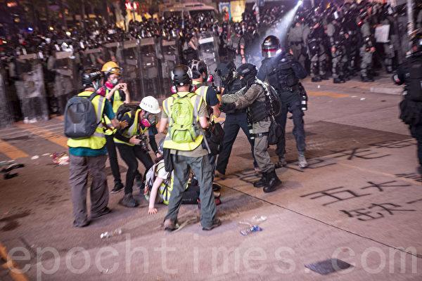 2019年9月29日,全球24國家、65個城市舉行「全球連線-共抗極權」遊行,圖為香港,遊行隊伍經過灣仔遭遇警方武力清場,有記者走避不及跌倒。(余鋼/大紀元)