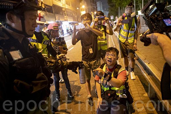 2019年9月29日,全球24個國家、65個城市舉行「全球連線-共抗極權」遊行,圖為香港,遊行隊伍經過灣仔遭遇警方武力清場,有記者走避不及跌倒。(余鋼/大紀元)
