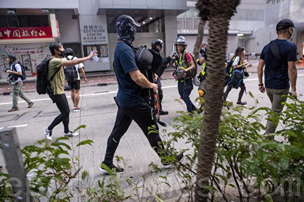 2019年9月29日,全球24個國家、65個城市舉行「全球連線-共抗極權」遊行,圖為香港,遊行隊伍經過灣仔遭遇警方暴力清場,有警察裝扮成抗爭者(中,穿深藍色上衣者),從背包裏掏出長槍。(余鋼/大紀元)
