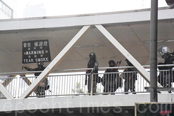 2019年9月29日,「全球連線-共抗極權」遊行活動。圖為防暴警察在香港灣仔天橋上向抗爭者發射布袋彈和催淚彈。(孫明國/大紀元)