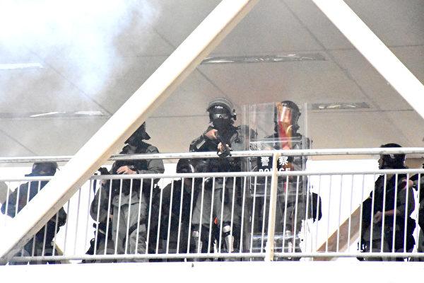 2019年9月29日,「全球連線-共抗極權」遊行活動。防暴警察在香港灣仔天橋上向抗爭者發射布袋彈和催淚彈。(孫明國/大紀元)