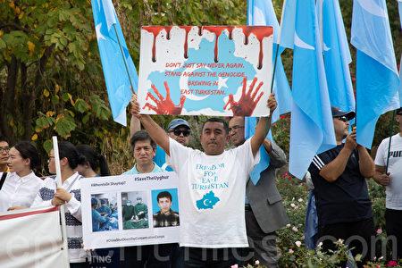 抗議民眾手舉標語,要求中共停止種族迫害。(林樂予/大紀元)