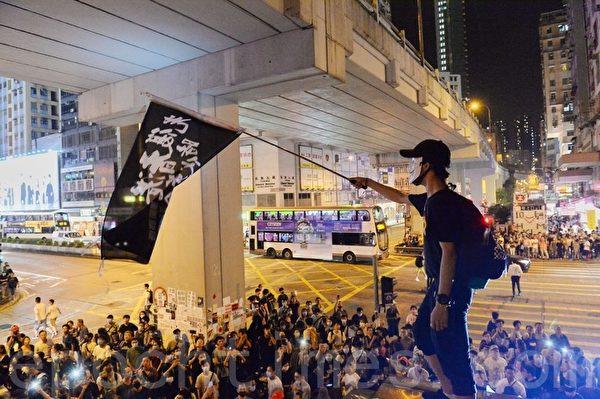 2019年9月30日,香港民眾紀念「831太子站事件」,有人爬上太子站出口,展示寫有「時代革命,光復香港」的旗幟表達訴求。(蔡依帆/大紀元)