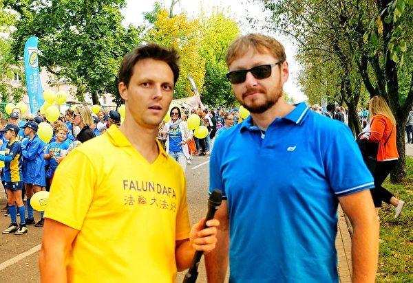 Krzysztof Kowalski先生(右)喜歡法輪功學員的舞龍表演。(明慧網)