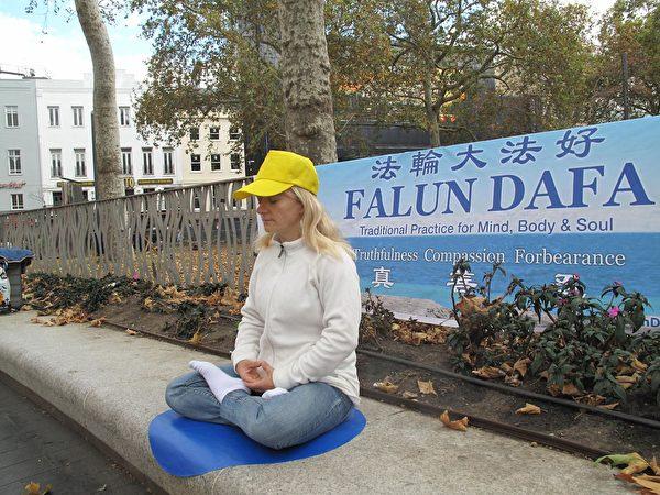 2019年9月1日,瑞士法輪功學員丹尼絲(Denise)在倫敦萊斯特廣場展示法輪功功法。(明慧網)