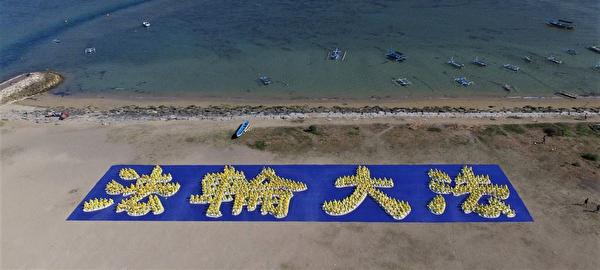 在登巴剎沙努爾海灘上,數百位法輪功學員排成「法輪大法」字型,從上空往下俯覽,場面壯觀。(明慧網)