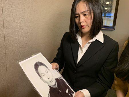 江莉展示她父亲江锡清的照片。