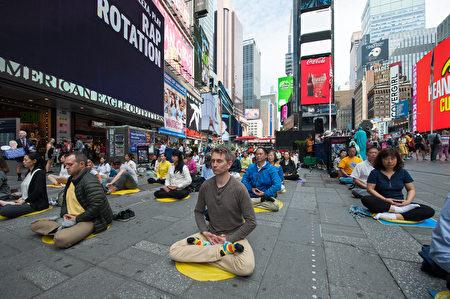 中西法輪功學員在紐約著名景點時代廣場煉功弘法,圖為學員在煉第五套功法——神通加持法。(大紀元)