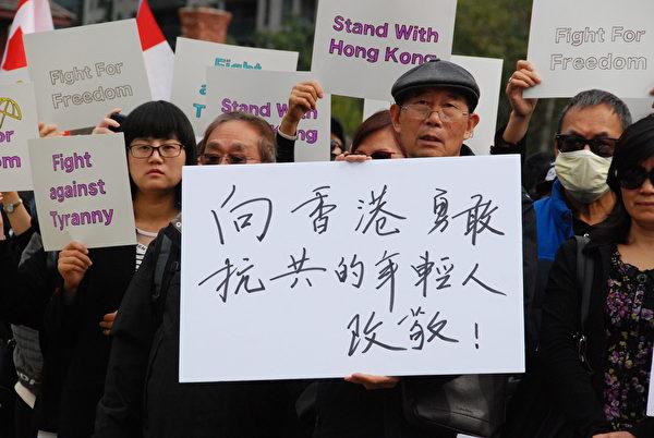 參加遊行的民眾手持「向香港勇敢抗共的年輕人致敬!」的標語。(伊鈴/大紀元)