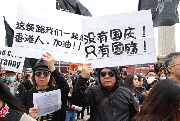 參加遊行的民眾手持「沒有國慶!只有國殤!」「這條路我們自己走,香港人,加油!」的標語。(伊鈴/大紀元)