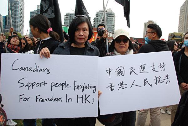參加抗共遊行的民眾,表明自己要和香港人站在一起。(伊鈴/大紀元)
