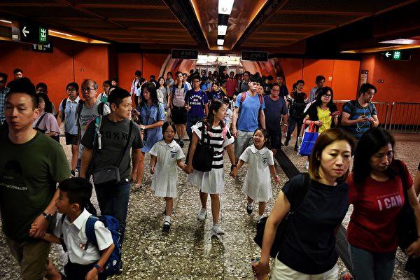 2019年9月2日,港鐵東區北角渣華道車站現大批持長盾防暴警察。圖為該地鐵站出閘民眾。( LILLIAN SUWANRUMPHA/AFP/Getty Images)