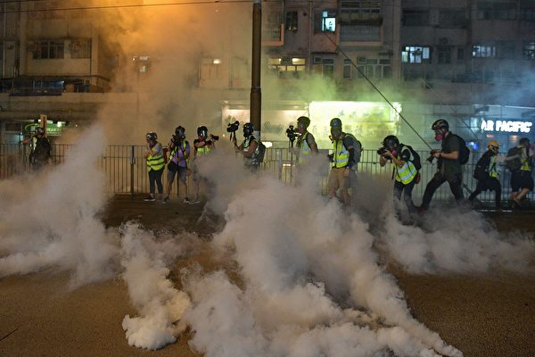 9月21日,大批民眾聚集在元朗街上,警察發催淚彈驅離,記者們也被煙霧籠罩。(NICOLAS ASFOURI/AFP/Getty Images)