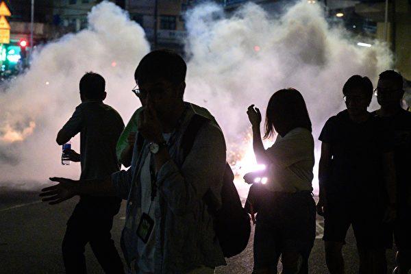 9月21日,大批民眾聚集在元朗街上,警察發催淚彈驅離。一名男子捂著臉。(PHILIP FONG/AFP/Getty Images)