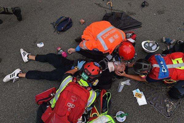9月29日,港警瘋狂抓人。圖為受傷的抗爭者在接受救護人士的幫助。(NICOLAS ASFOURI/AFP/Getty Images)