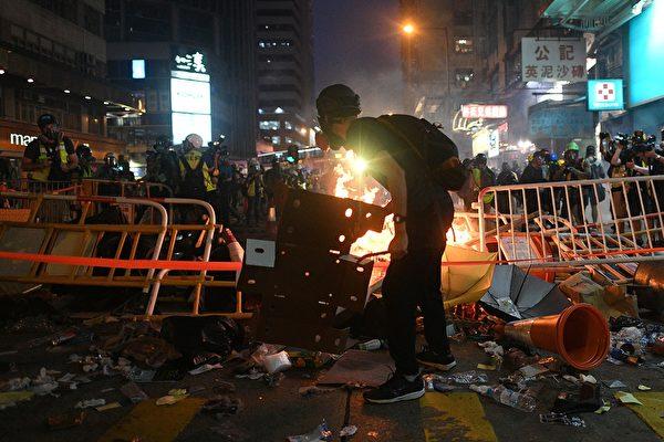 9月29日晚,港警狂放催淚彈,示威者扔碎片到火堆裡。(MOHD RASFAN/AFP/Getty Images)