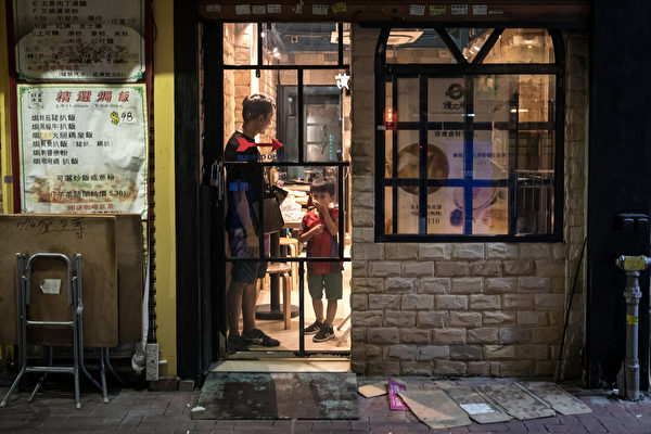 9月21日夜,大批民眾聚集元朗抗議7.21白衣人襲擊,警方不作為,警察施放催淚彈驅離,街坊關門,孩子也捂著嘴。 (Chris McGrath/Getty Images)