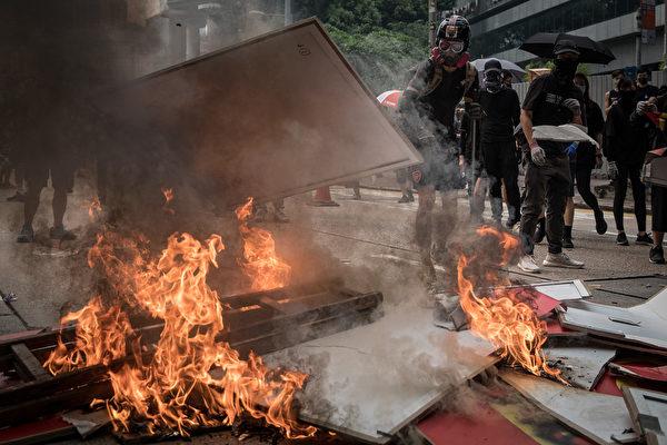 """9月29日,有黑衣人爬上金钟廊天桥旁的行人楼梯顶,天桥上的""""十一""""庆祝标语被毁。(Chris McGrath/Getty Images)"""
