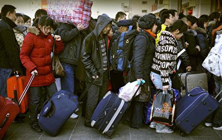 圖為中國新年期間,北京站門口等待返鄉的旅客,人挨人地等著進站候車。(PETER PARKS/AFP/Getty Images)