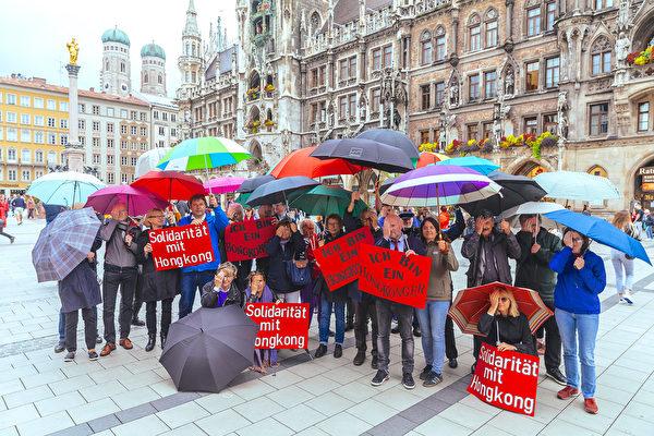2019年9月9日下午,二十多位德國慕尼黑市議會社民黨(SPD)議員在著名的瑪琳廣場市政廳前合照,手摀住右眼,聲援香港。(黃芩/大紀元)
