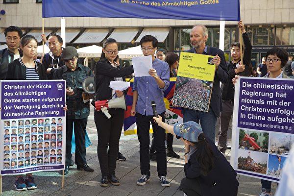 2019年9月14日,多團體齊聚德國科隆譴責中共,聲援香港民眾五大訴求。圖為保護宗教與人權協會代表在集會上發言,右邊舉黃色牌子的是牧師羅蘭特‧庫訥(Roland Kuhne)。(黃芩/大紀元)