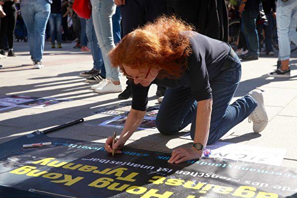 2019年9月29日,香港留學生、港僑等各界人士在慕尼黑瑪琳廣場集會,聲援香港民眾反極權的運動。圖為鮑澤議員簽名聲援香港民眾。(黃芩/大紀元)