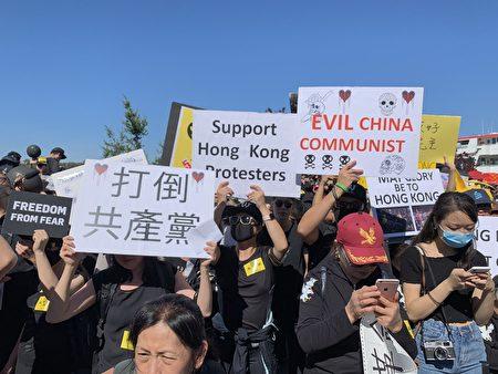 """集会现场,人们举起各式表达心声的标语,包括""""光复香港、时代革命"""",""""反赤纳粹""""(Anti-Chinazi),""""天灭中共"""",也有英文的标语写着""""英国人用100年将香港变成世界最伟大的城市,中共用100天毁掉香港。"""""""