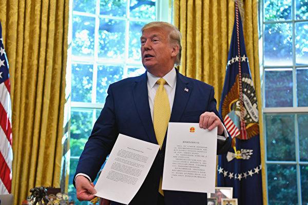 特朗普接過信封後立即打開,共兩頁,分別用中文、英文書寫。(Nicholas Kamm/AFP)