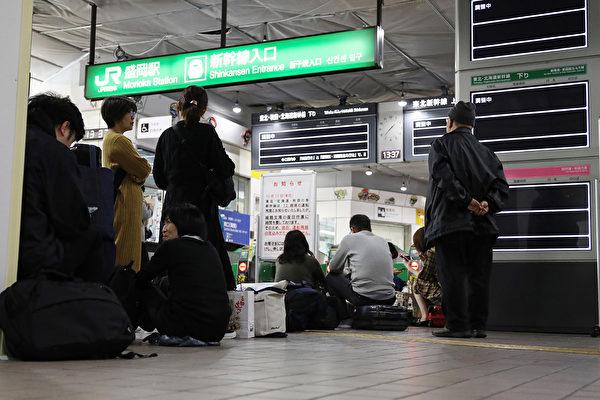 人們在10月13日在巖手縣盛岡市的車站等待火車恢復運行。(STR/JIJI PRESS/AFP)