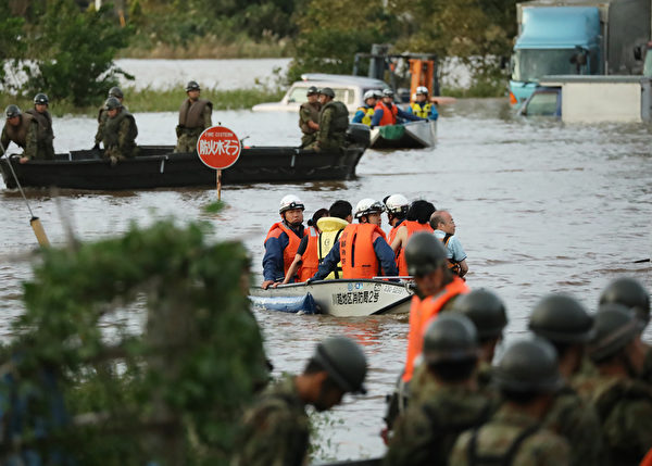 圖為10月13日,救援人員在埼玉縣幫助疏散居民。(STR/JIJI PRESS/AFP)