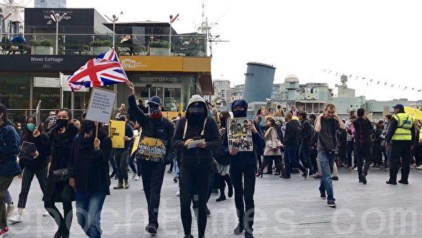 倫敦10.5反禁蒙面法遊行開始後陸續有更多的港人加入隊伍,估計最高峰時有近千名民眾參加。他們手牽手高叫口號並唱出《願榮光歸香港》,吸引市民注意,更獲得不少掌聲支持。(唐詩韻/大紀元)