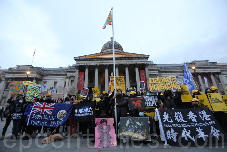 10月5日,參加集會的港人在特拉法加廣場啟動「連儂旗」升旗儀式。幟旗在港人伴唱《願榮光歸香港》的歌聲下飄升在倫敦的天空中,場面令人感動。(唐詩韻/大紀元)