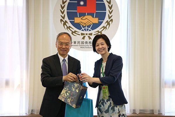 10月7日,僑委會主席吳新興(左)致贈紀念品給新唐人代表團團長方菲。(僑委會提供)