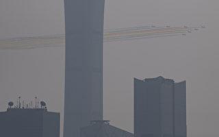 10月1日中共举行阅兵式,北京城被阴霾笼罩。图为天空中的彩色飞机阵。(NOEL CELIS / AFP)