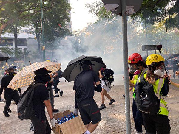 2019年10月20日,九龍區大遊行防暴警察向抗爭者發射催淚彈,抗議者運水。(駱亞/大紀元)