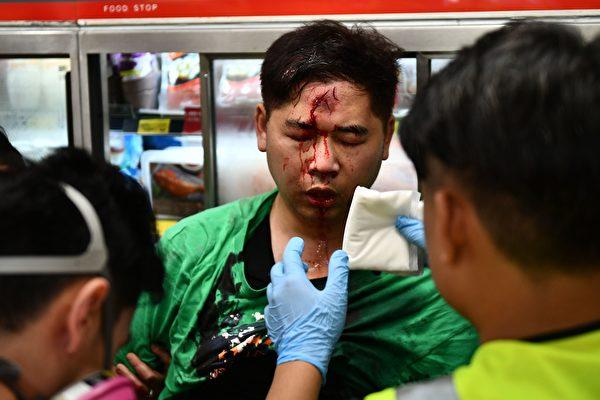 10月13日日,港人抗爭中,醫護人員在幫助一為被警察打傷的男子。(ANTHONY WALLACE/AFP via Getty Images)