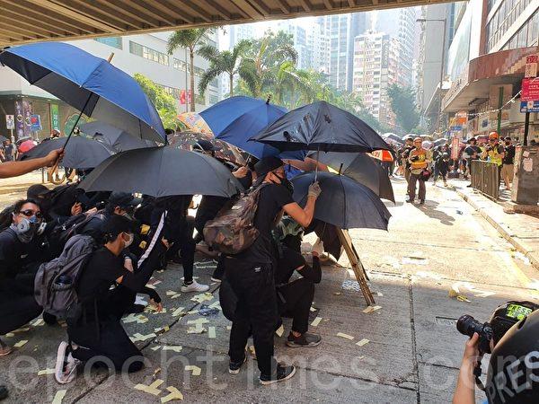 2019年10月1曰,香港,遊行隊伍到灣仔民眾撐起雨傘佈陣。(孫明國/大紀元)
