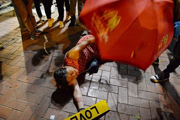 2019年10月1日,「十一」港人六區抗暴政活動。銅鑼灣警察近距離對女子眼睛用胡椒噴霧,女子痛的倒地。(宋碧龍/大紀元)